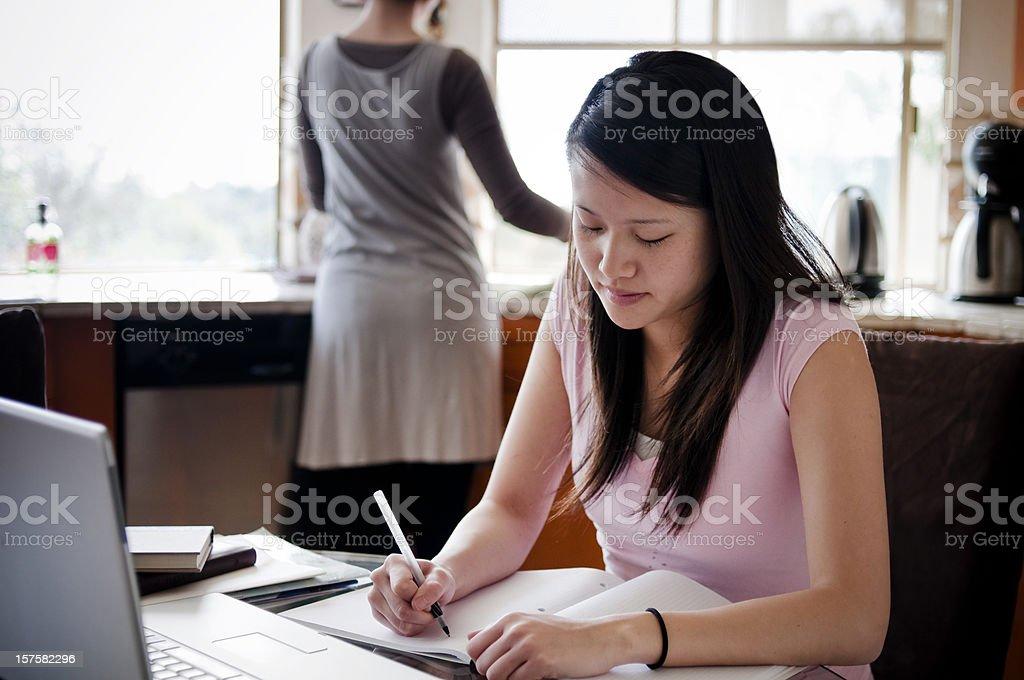 Asian teenage girl doing homework stock photo