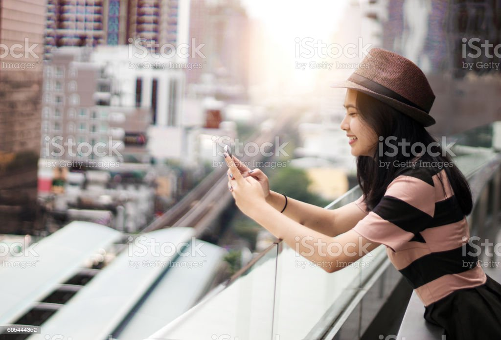 asian teenage use mobile phone in town stock photo