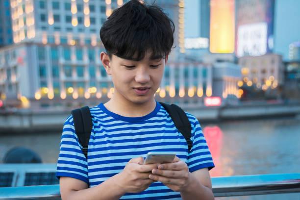 Asian teenager boy using phone. stock photo