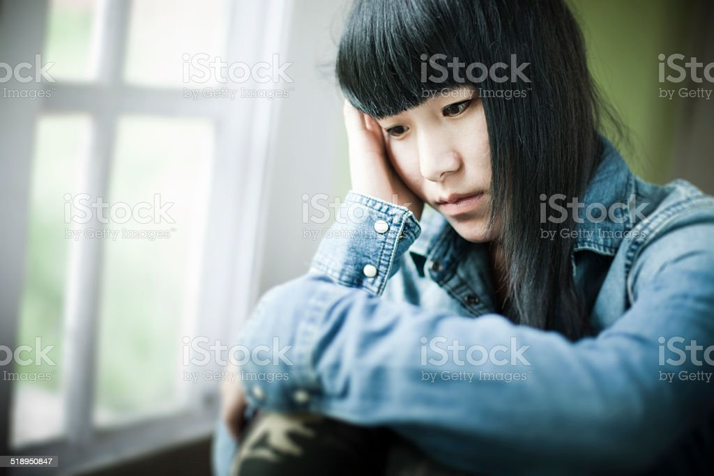 Asian teenager girl sitting near window with sadness. stock photo