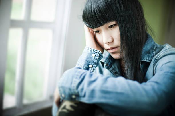 Asiatische teenager-Mädchen sitzt in der Nähe von Fenster mit Traurigkeit. – Foto