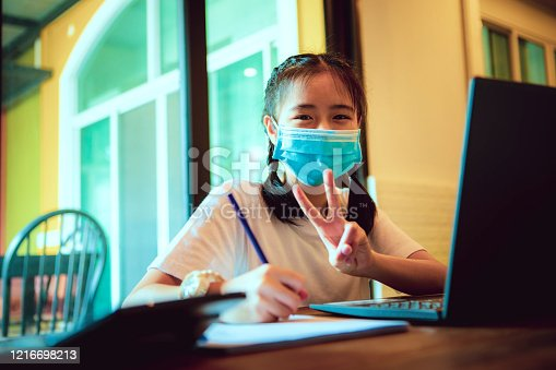 asian teenager studying at home by computer laptop while covid-19 virus infected  global