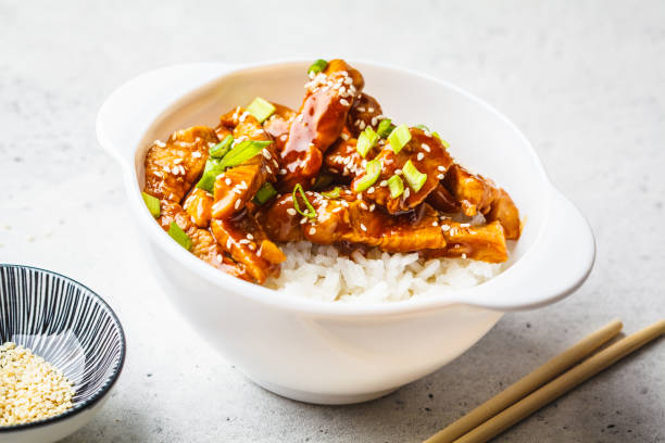 Asian teriyaki chicken with rice, sesame and green onions in white bowl. stock photo