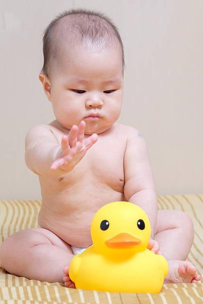 Tailandés asiática niña bebé jugando con pato de goma amarilla - foto de stock