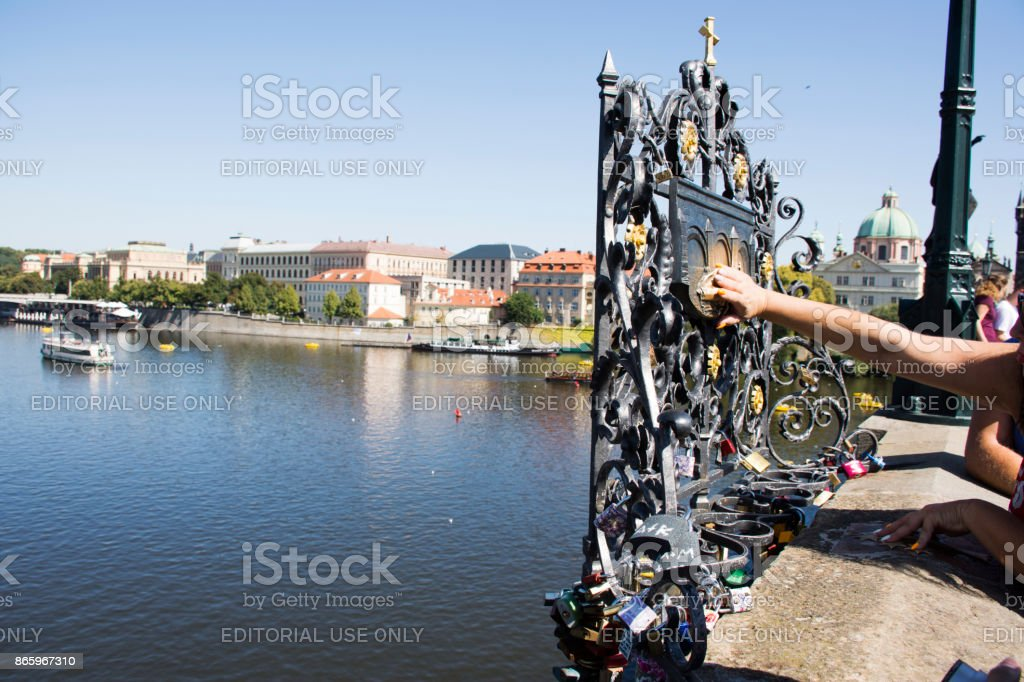 Asian thai woman touching plaque with saint john of nepomuk and padlocks engraved stock photo