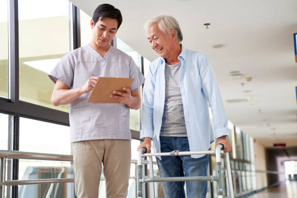 asian therapist working with senior patient in rehab center stock photo