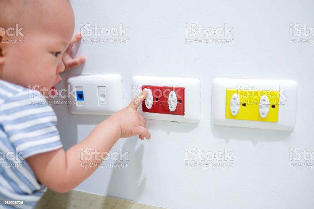 Asiatischen Kleinkind Baby junge Kind spielen mit elektrischen Stecker. – Foto