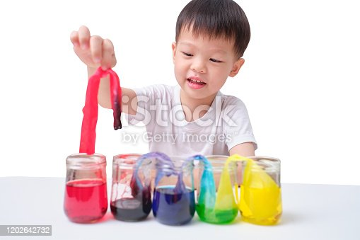 544351868 istock photo Asian toddler boy making Color Changing Walking Water Experiment, Glasses in row with colored water and wet paper between, Easy Kids Science Experiment concept 1202642732