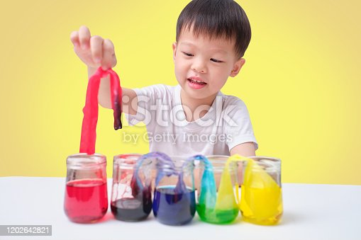 544351868 istock photo Asian toddler boy making Color Changing Walking Water Experiment, Glasses in row with colored water and wet paper between, Easy Kids Science Experiment concept 1202642821