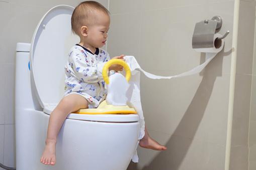 Boy, child sitting on toilet reading a book. - Stock Photo
