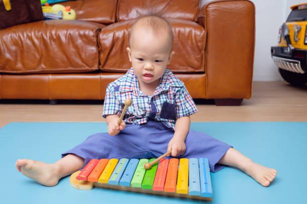 asiatische kleinkind spielt ein hölzernes spielzeug xylophon - lautbildungsspiele stock-fotos und bilder