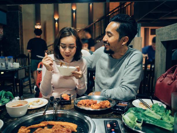 レストランで娘と一緒に韓国のバーベキュービュッフェを食べるアジアの観光客カップル。 - 韓国文化 ストックフォトと画像