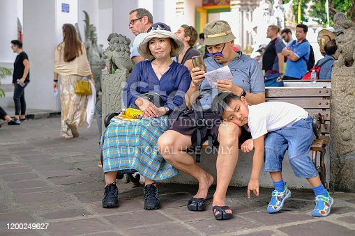 Asian tourist family visiting Thailand's famous historical Buddhist Wat Pho temple, take a rest on a garden seat inside the temple complex of the ancient and much visited Buddhist temple of Wat Pho. Interesting relationship between modern tourists and the cultural, historical surroundings of one of Bangkok's famous tourist sites.