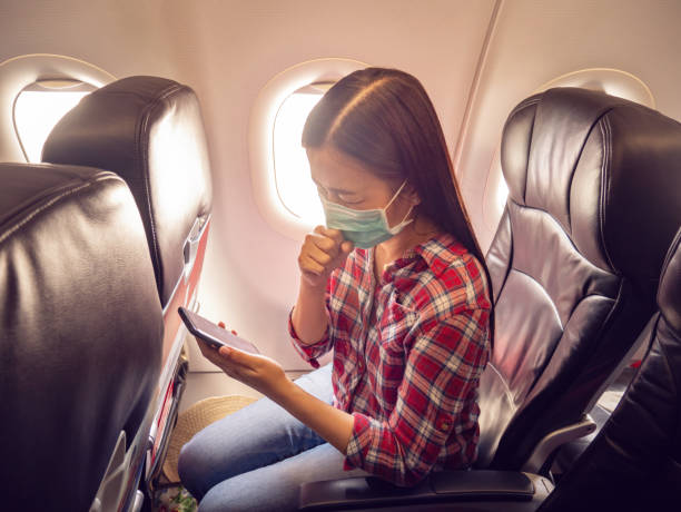 asian tourist feeling sick, coughing ,wearing mask to prevent during travel time by airplane for protect from the new coronavirus 2019 infection outbreak situation - covid flight imagens e fotografias de stock