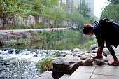 istock Asian tourist girl rope her shoelace near beautiful river in big city located at  Cheonggyecheon Stream in South Korea. 1315936789