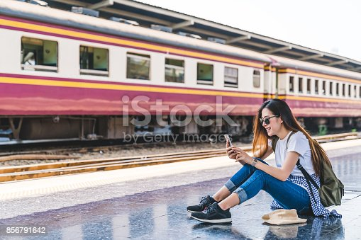istock Asian tourist teenage girl at train station using smartphone map, social media check-in, or buy ticket booking. Modern travel app technology, lone traveler, Summer vacation railroad adventure concept 856791642