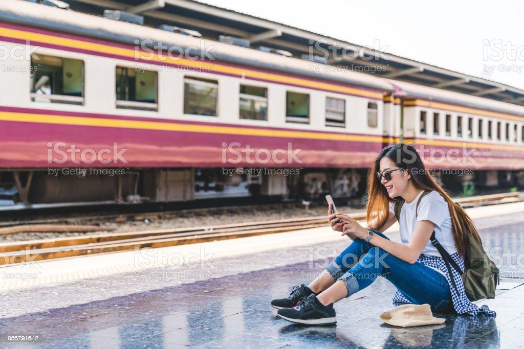 Asiatische Touristen Teenager-Mädchen am Bahnhof mit Smartphone-Karte, social-Media-Check-in oder Tickets kaufen. Moderne Travel app Technologie, Einsamer Reisender, Sommer-Urlaub-Eisenbahn-Abenteuer-Konzept – Foto