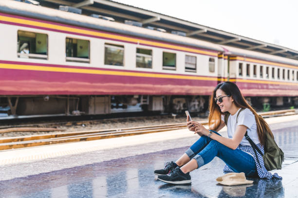 Asian tourist teenage girl at train station using smartphone map, social media check-in, or buy ticket booking. Modern travel app technology, lone traveler, Summer vacation railroad adventure concept stock photo
