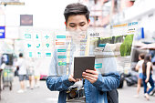 Asian tourist using mobile appication technology booking hotel online