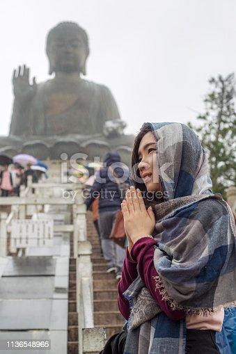 Asian tourist visiting Tian Tan Buddha in Ngong PingLantau Island, Hong Kong, worshipping in rainny day. The Big Buddha, is a large bronze statue of Buddha Shakyamuni, one of the most visited travel destination in HK