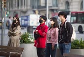 Barcelona, Spain - March 13, 2020: Asian tourists in Barcelona wearing virus protection face masks in Barcelona.