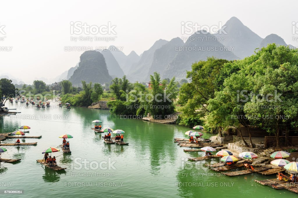 Asian tourists traveling by bamboo rafts along the Yulong River stock photo
