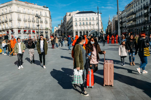 Asian tourists with luggage wear surgical mask in Madrid, Spain - Coronavirus concept stock photo