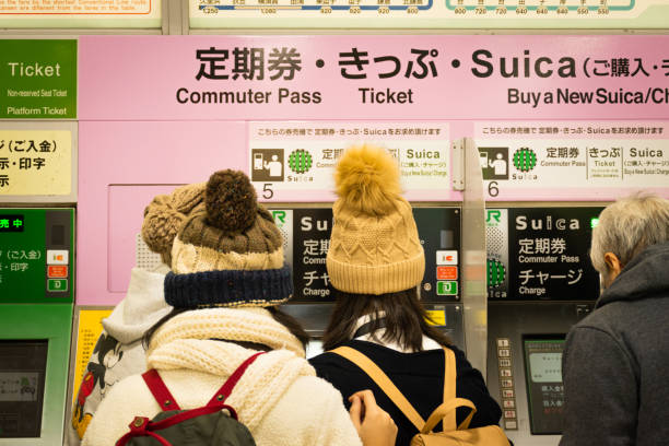 "Asian tourists with vending machine in rear view. Tokyo, Japan - 12 DEC 2017: Asian tourists trying to understand that how to buy and use ""​Suica"", the prepaid e-money card for moving around and shopping at Tokyo main station. train ticket stock pictures, royalty-free photos & images"