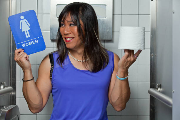 Asian Transgender female happy and smiling holding a women's restroom sign and a roll of toilet paper, Sitting in a restroom stall. stock photo