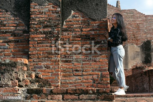 Asian millennial travel influencer girl hiding behind red brick wall in ancient city - Young diverse pretty woman smiling and having fun exploring with copy space - weekend and lifestyle concept