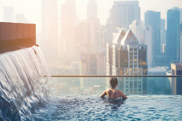 Asian travel. young woman enjoying the city view from roof top swimming pool. Asian travel. young woman enjoying the city view from roof top swimming pool. infinity pool stock pictures, royalty-free photos & images