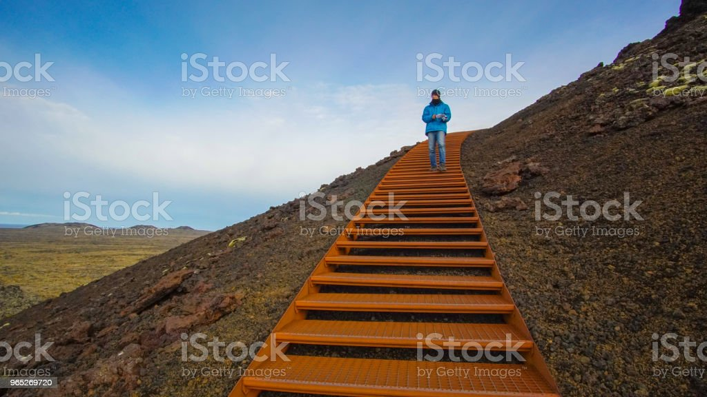 Asian traveler man and volcano crater. Abstract top success royalty-free stock photo