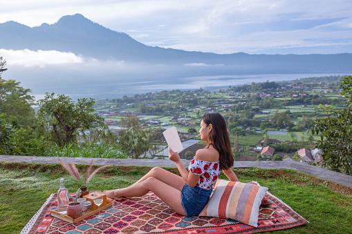 Asian Traveler Reading Book While Picnic