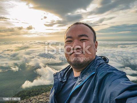 Asian Traveler Take a Selfie with Beautiful Sunrise Sky on the mountain