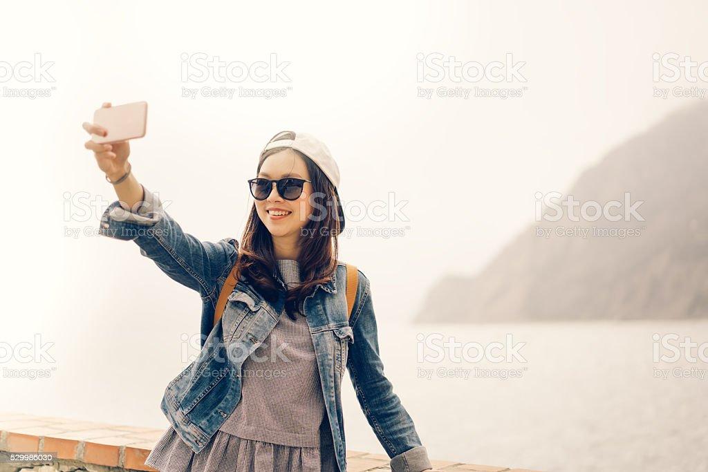 Asian traveler taking selfie with ocean view, soft warm tone