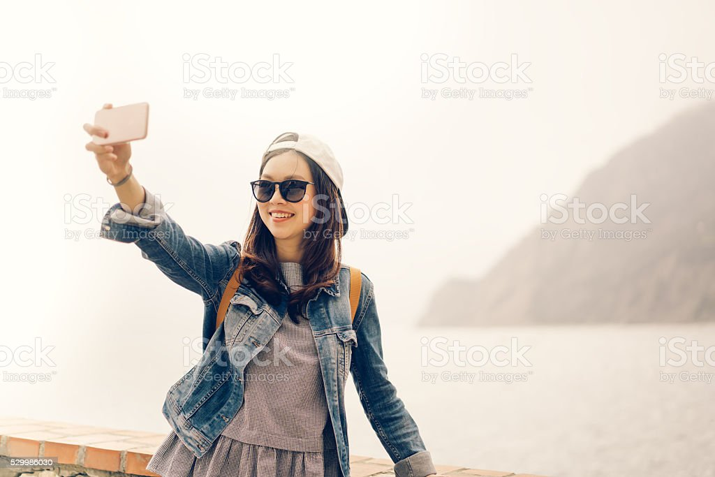 Asian traveler taking selfie with ocean view, soft warm tone stock photo