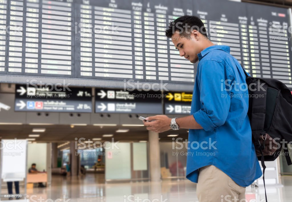 Asian traveler using the smart mobile phone for check-in at the flight information screen in modern an airport, travel and transportation with technology concept. stock photo