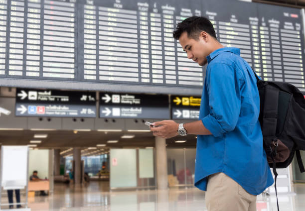 asian traveler using the smart mobile phone for check-in at the flight information screen in modern an airport, travel and transportation with technology concept. - aids healthcare foundation foto e immagini stock
