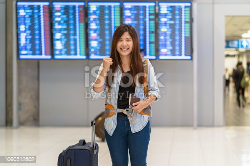 842907838 istock photo Asian traveler with luggage with passport walking over the flight board for check-in at the flight information screen in modern an airport, travel and transportation with technology concept. 1060512802