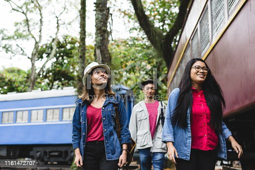 Asian travelers ready to board the train ride (Valença, RJ, Brazil).  These are old trains that are in a public square in the city of Valença (small town in the interior of the State of Rio de Janeiro) They are exposed in this square with free access.