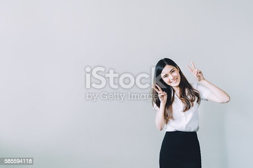 istock Asian university girl doing funny rabbit pose, with copy space 585594118