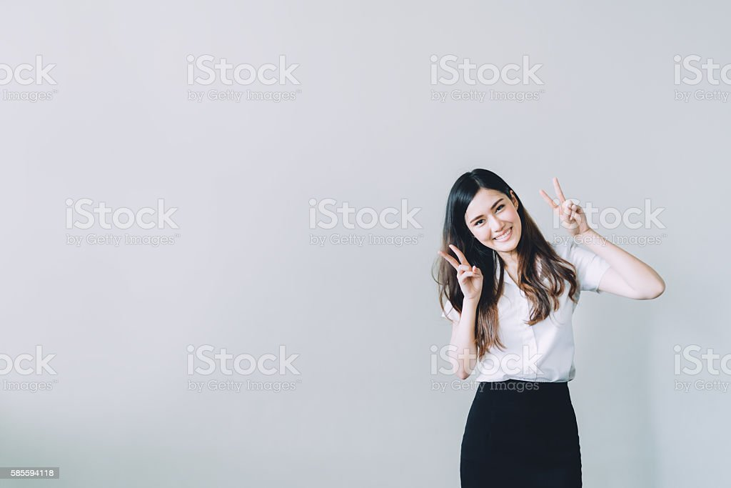 Asian university girl doing funny rabbit pose, with copy space stock photo