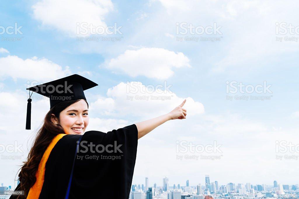 Asian university graduate student woman pointing copy space on sky royaltyfri bildbanksbilder