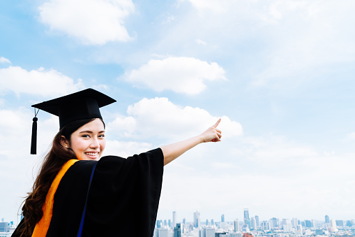 istock Asian university graduate student woman pointing copy space on sky 590290270
