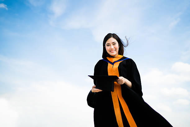 Asian university graduate student woman smiling in graduation academic dress stock photo