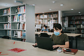 istock asian university student studying in library observing social distancing 1281913376