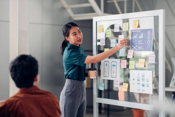 asian ux developer and ui designer presenting mobile app interface design on whiteboard in meeting at modern office.Creative digital development mobile app agency.digital transformation stock photo