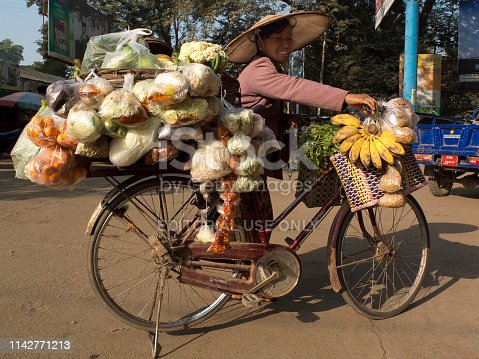 Mandalay, Myanmar - February 4, 2016: Street vendor with her bicycle. She is selling fruits and vegetables.