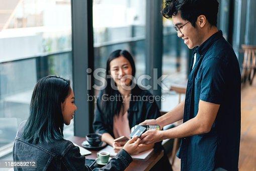 Asian waiter receiving cashless payment via mobile phone