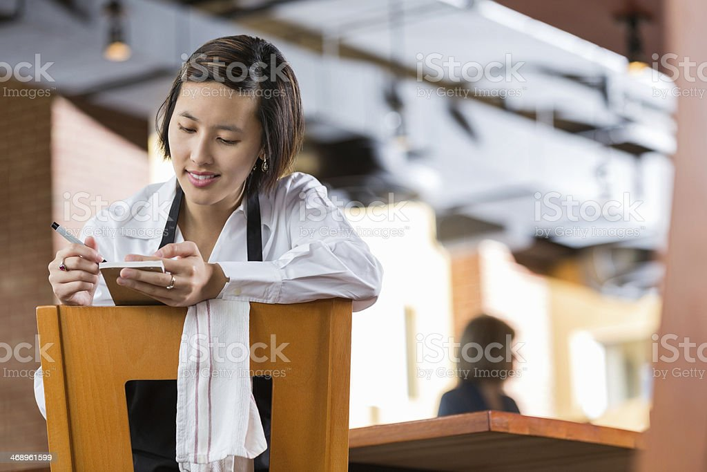 Asian waitress looking at tickets in restaurant after closing time stock photo